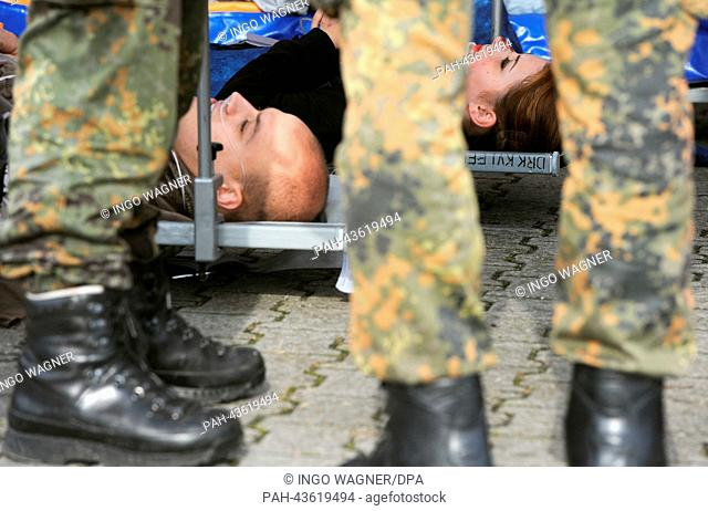 Rescuers of the Federal Armed Forces and the German Red Cross (DRK) care for the made-up impersonators of injured people during an emergency drill at a barrage...