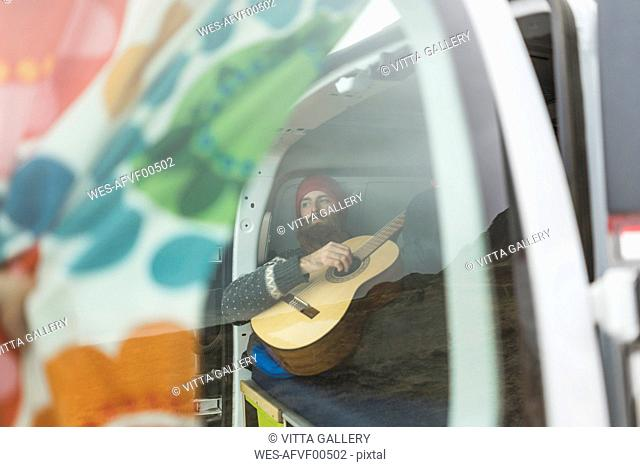 Man lying in van playing guitar