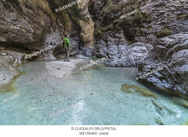 Dolomites, Belluno, Veneto, Italy. An hiker looking the turquoise water in Val Soffia, Mis valley