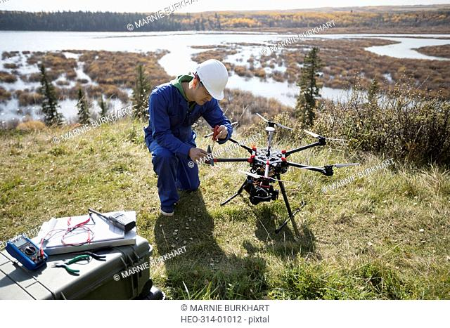 Surveyor repairing drone equipment on hilltop overlooking lake
