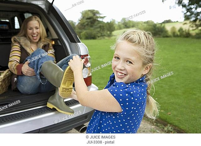 Girl 9-11 helping mother remove wellington boots, woman sitting in boot of car, smiling