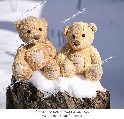 two small teddy bears are sitting on a stump in a snowy winter day