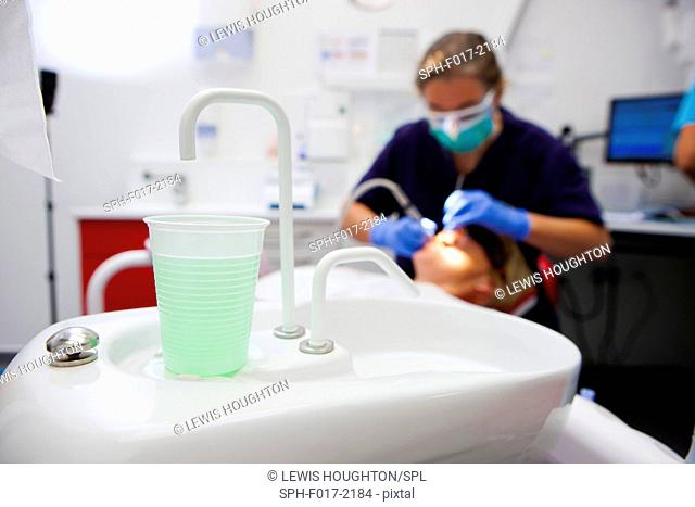MODEL RELEASED. Dentist's sink in foreground with patient having teeth examined