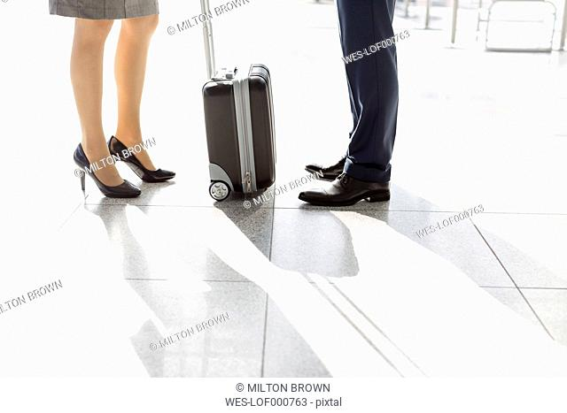 Low section of businessman and businesswoman at the airport