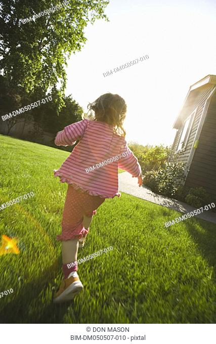Back of girl running in back yard