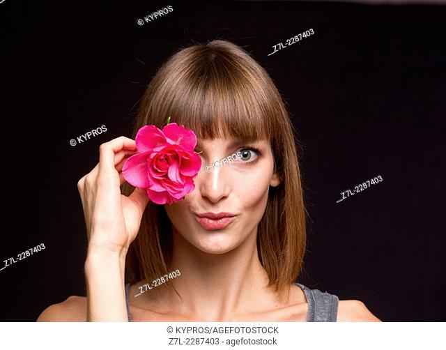 Portrait of young woman holding flower