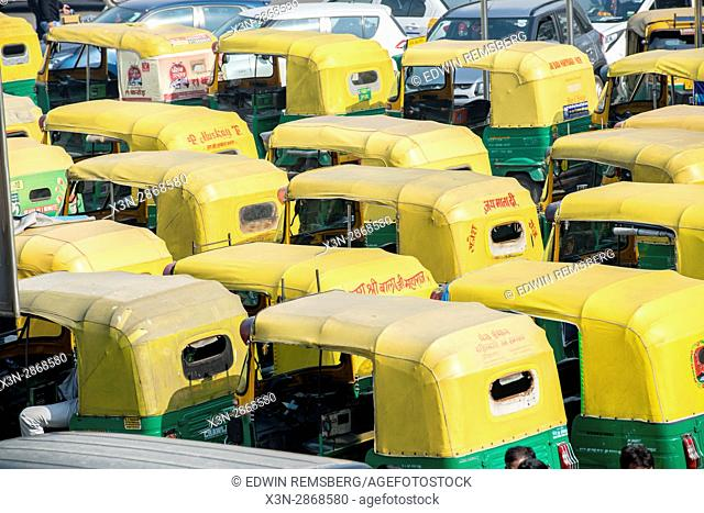 Yellow topped taxi cars are lined up in downtown New Delhi, India