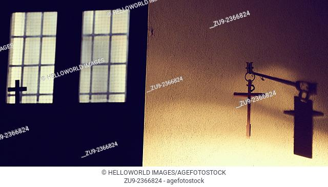 Simple cross hanging on wall with shadow and cross in window light, Milan, Italy, Europe