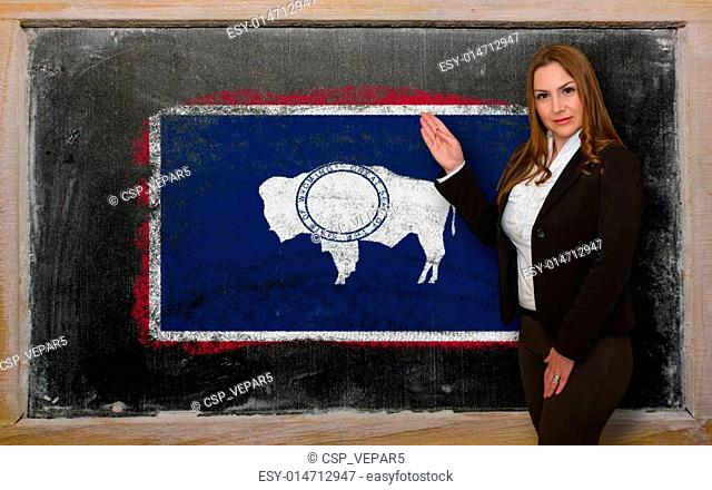Successful, beautiful and confident woman showing flag of wyoming on blackboard for marketing research, presentation and tourist advertising