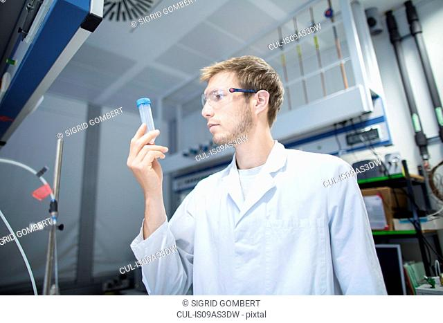 Young male scientist looking at sample bottle in lab