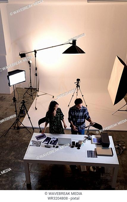 Male and female photographer looking at photographs