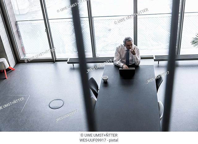Senior manager in office using smartphone and laptop