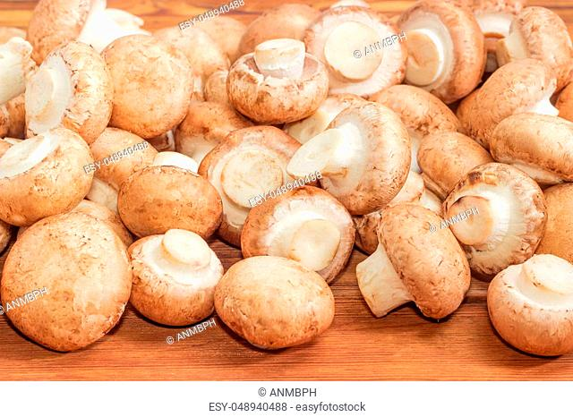 Pile of the fresh cultivated brown mushrooms on a wooden surface at selective focus