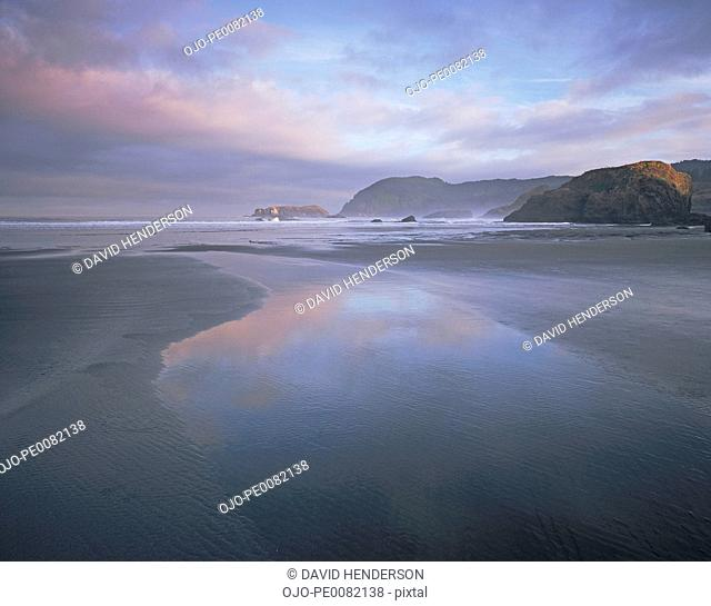 Clouds reflected in still water on beach