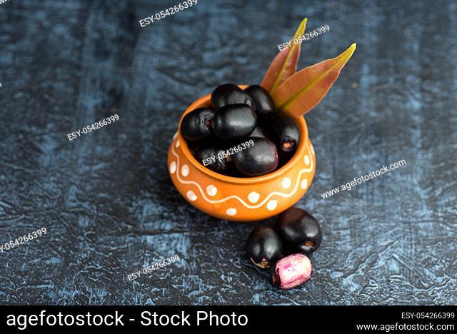 Jambolan plum or jambul or Jamun fruit, Java plum (Syzygium cumini) with leaf on stone textured background