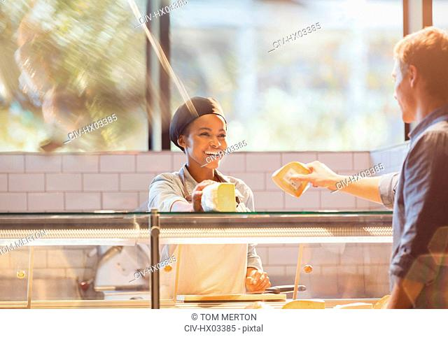Smiling female worker serving customer at cheese counter in grocery store market