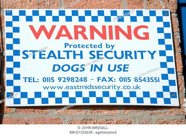 Sign warning that the premises are being protected by a security company that uses dogs
