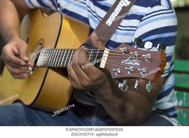 Closeup of man playing guitar