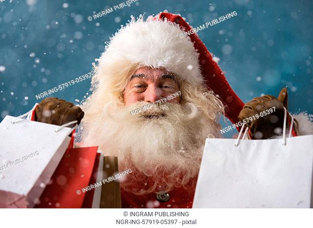 Photo of happy Santa Claus outdoors in snowfall holding shopping bags. Christmas sales and discount concept