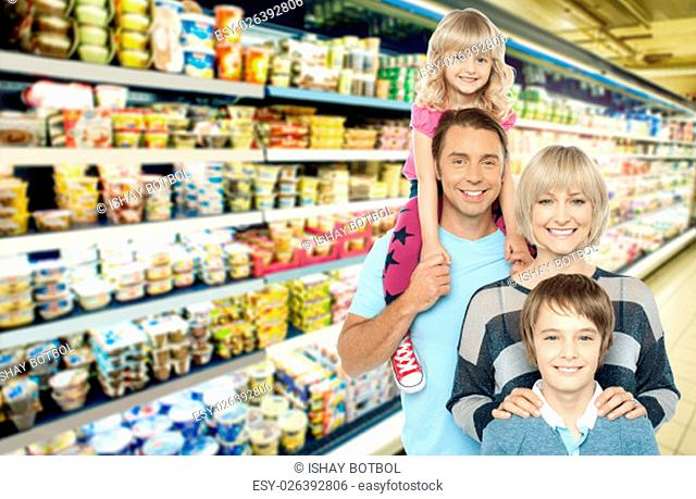 Image of young family grocery shopping in supermarket
