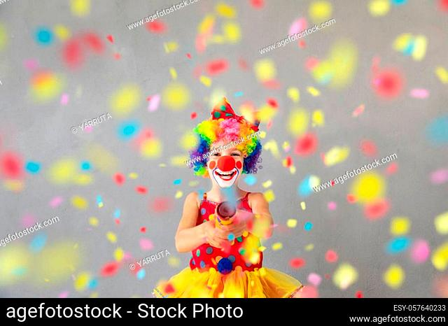 Funny kid clown with party poppers. Happy child playing at home. 1 April Fool's day concept