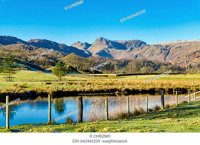 The Langdale Pikes seen from Elterwater with a fence and water in the foreground