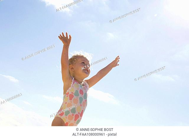 Little girl standing on beach with arms raised