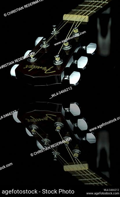 Close up image form a classic guitar on a mirror as background painted with light