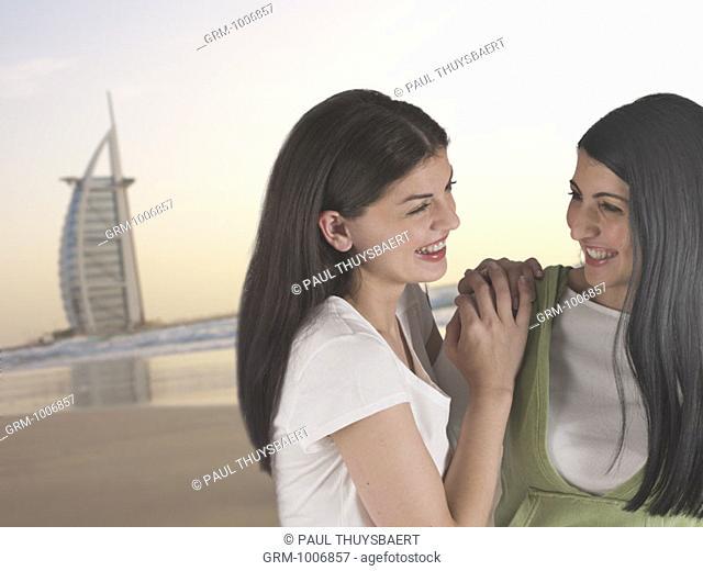 Two women on the beach in Dubai with Burj Al Arab Hotel in background