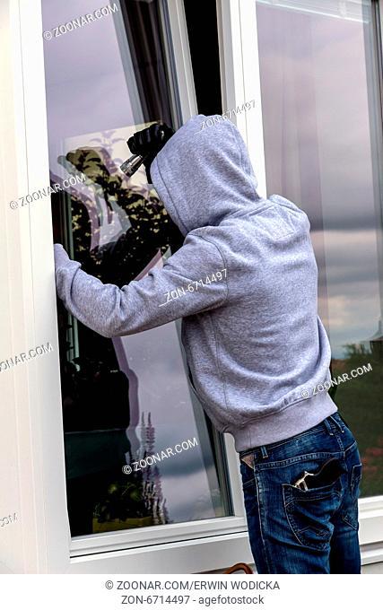Ein Einbrecher versucht bei einem offenen Fenster mit einer Brechstange einzubrechen
