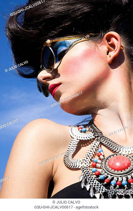 Profile Portrait of Young Adult Woman with Heavy Makeup Wearing Sunglasses and Large Necklace