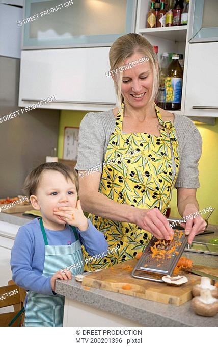 Boy eating grated carrots while mother grating carrots