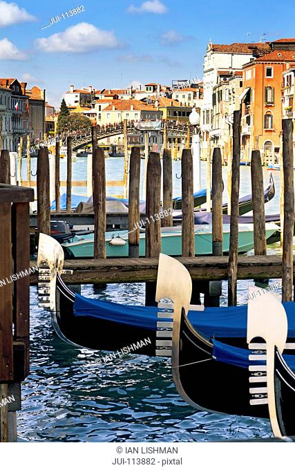 Gondolas moored in Grand Canal in front of architectural buildings in Venice, Italy