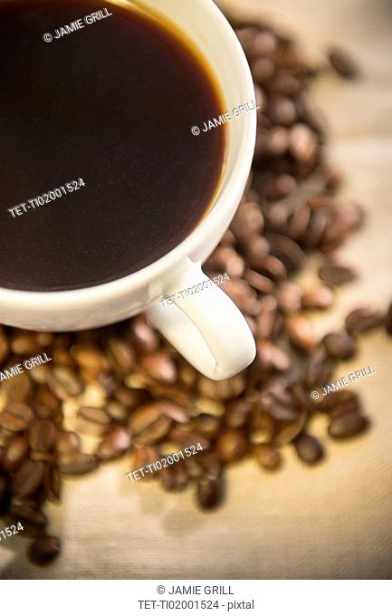 Studio shot of cup of coffee and roasted coffee beans
