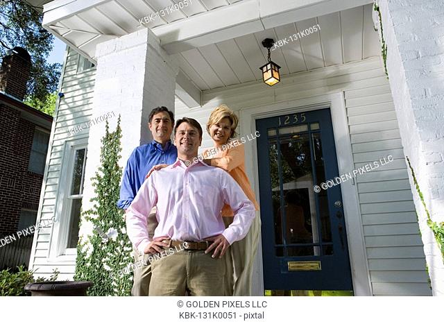 Portrait of a family standing outside a house