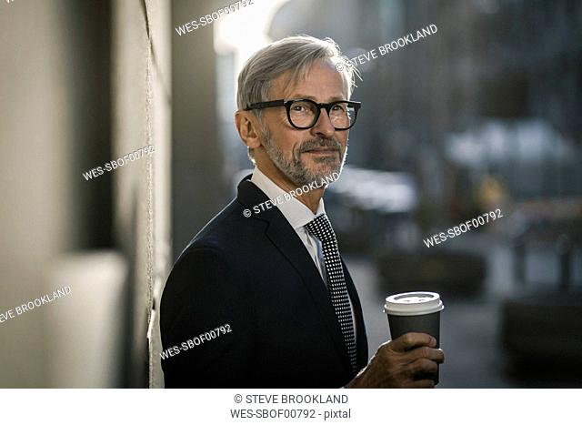 Grey-haired businessman in the city holding coffee to go
