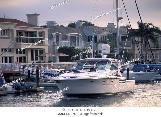 Luxury yacht Boat cruising through harbor channel next to waterfront homes at Newport Beach, California