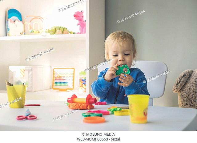 Portrait of baby girl playing with cutter and modeling clay