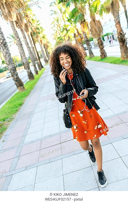 Portrait of laughing young woman with earphones talking on mobile phone while walking down a promenade