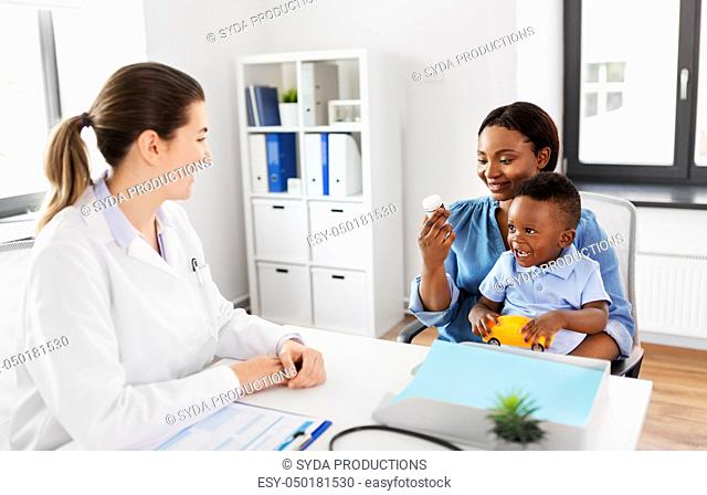 doctor and woman with baby and medicine at clinic