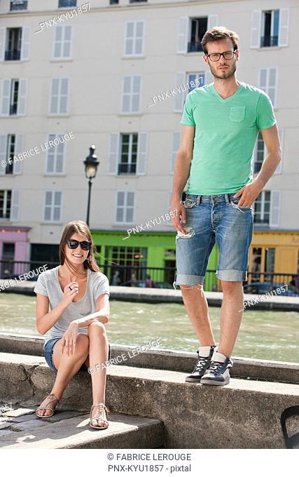 Couple on a ledge of a canal, Canal St Martin, Paris, Ile-de-France, France