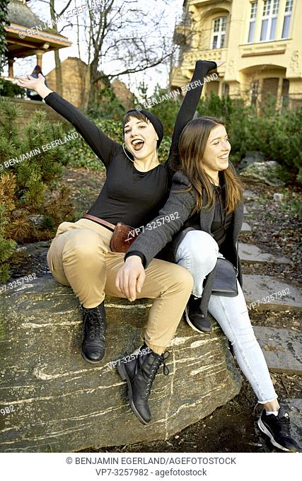 two women sitting together outdoors in park, in city Cottbus, Brandenburg, Germany