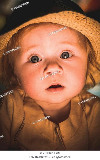 A cute baby. Sunlight on the child's face. A curious look of a little girl. Sad look of the child. Light from a candle. He looks carefully