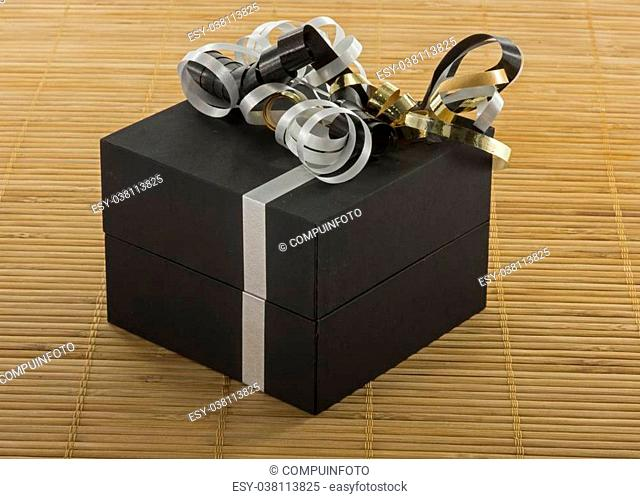 black box with white lines and golden silver bows as present