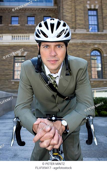 Businessman with bicycle in front of office building, Toronto, Ontario