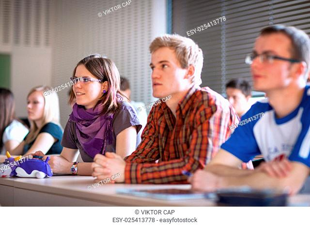 College students sitting in a classroom during class (shallow DOF; color toned image)