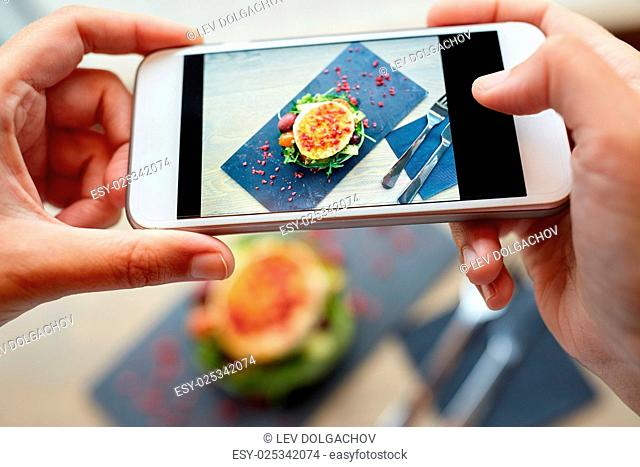 food, culinary, technology and people concept - woman hands with smartphone photographing goat cheese salad with vegetables and dried raspberries at restaurant...