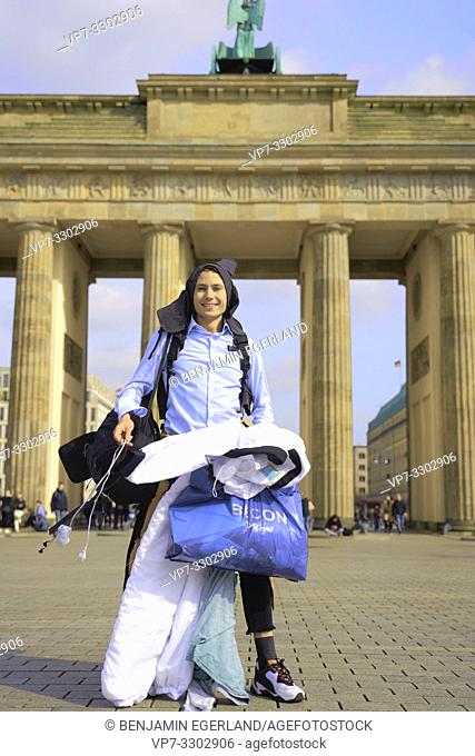 young tourist man, traveller, carrying too much baggage, in front of touristic sight Brandenburg Gate, in Berlin, Germany