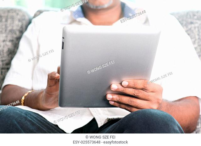 Modern technology. Mature Indian man using touch screen digital tablet computer at home. Asian people living lifestyle indoors