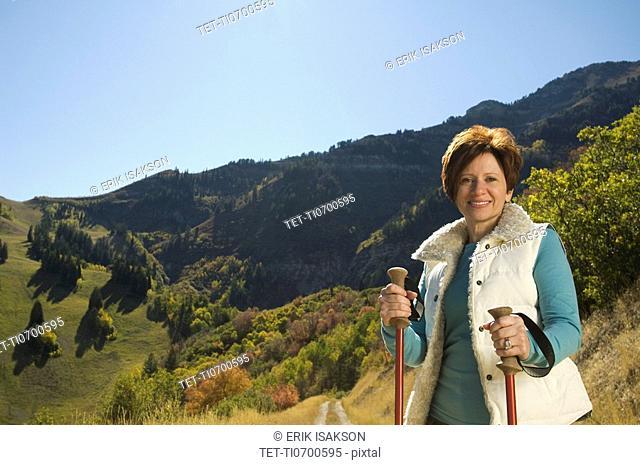 Senior woman holding hiking poles, Utah, United States